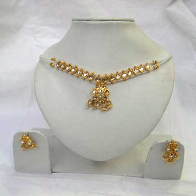 Reveal the mystery of beauty with this fabulous white kundan studded necklace set with matching earings.
